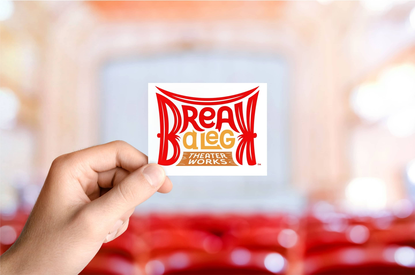 Break A Leg Theater logo on business card with stage background